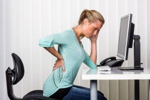 Woman sitting at her desk clasping her low back in pain