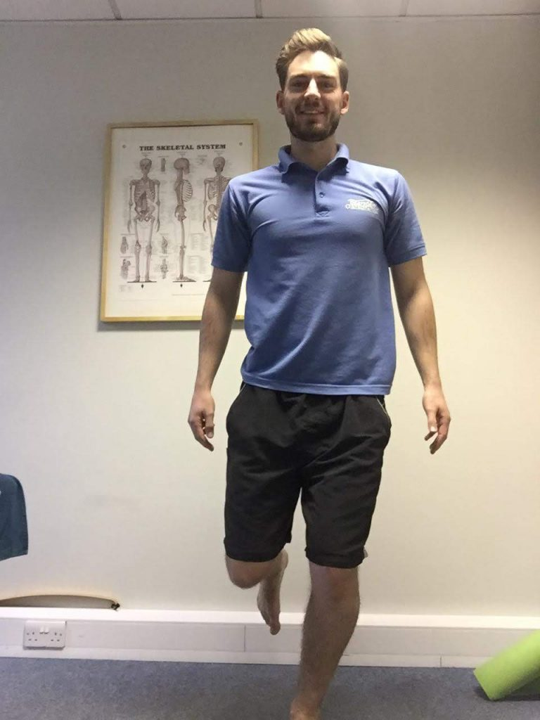 Our osteopath, Harry, showing you an exercise. Standing on one leg with the other bent at the knee