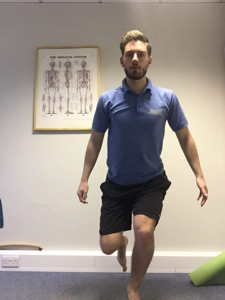 Harry demonstrating a knee exercise. He is standing on one leg with the other bend, lowering himself down with flexed toes