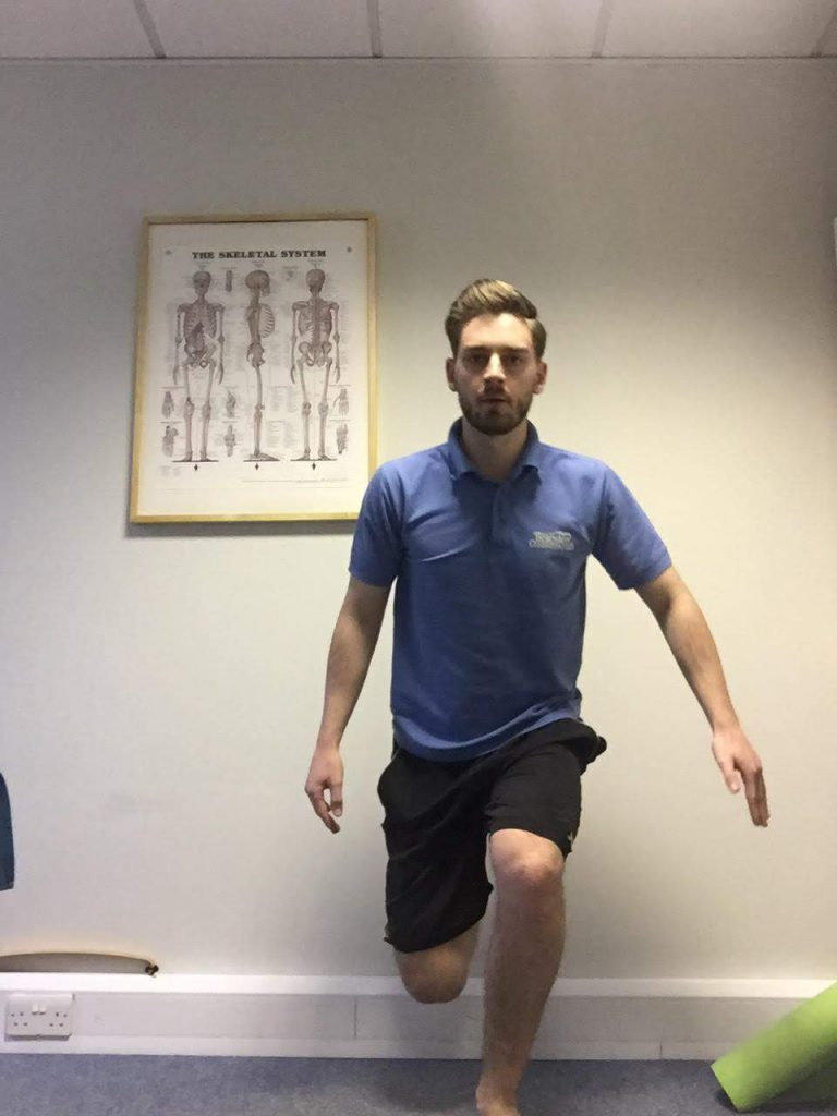 Harry showing a knee exercise. He is standing on one leg, the other is bent at the knee and he is lowering himself down