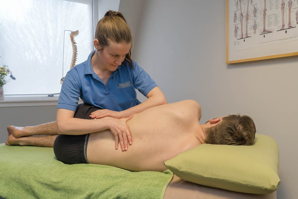 Osteopath Linda stretches Harry's lower back to ease out sciatica pain