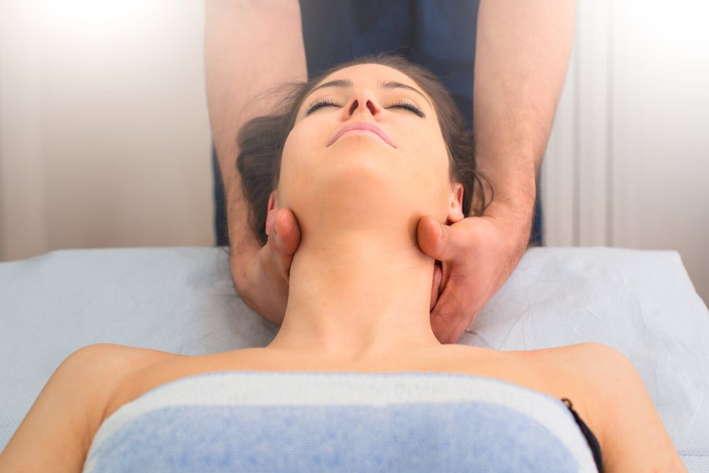 Therapist massaging the neck of woman In the by an osteopath in studio