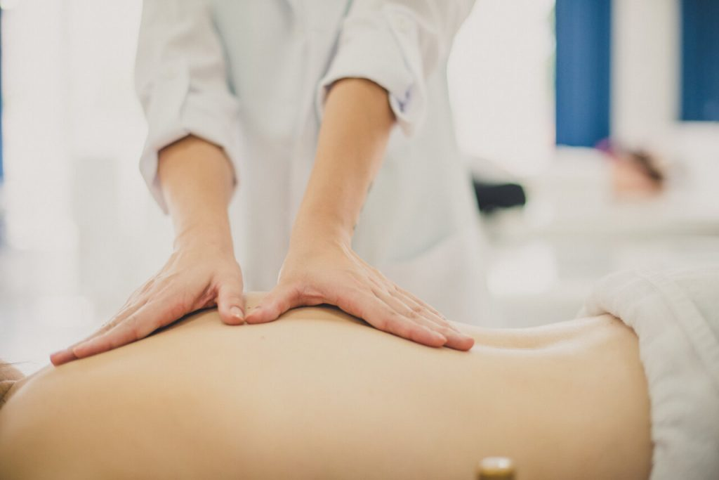 Osteopath applies gentle pressure to female's back to ease her pain