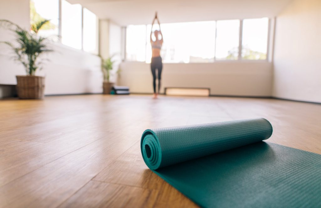 Exercise mat on floor with woman practising yoga in background. Close up of pilates mat in fitness center and blurred female at the back exercising.