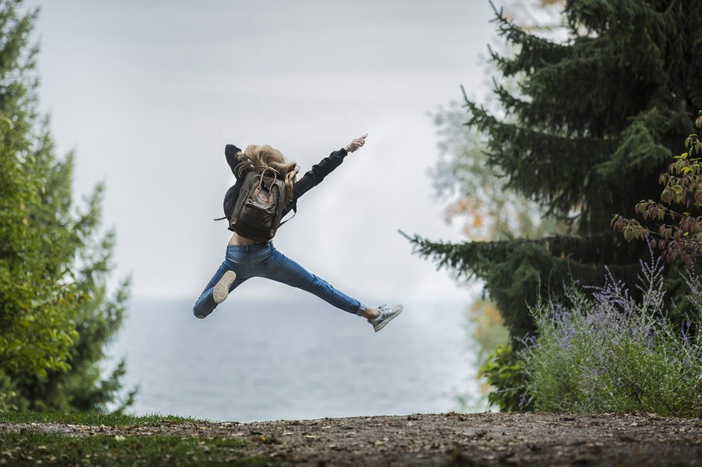 girl jumping, pain free, in the outdoors