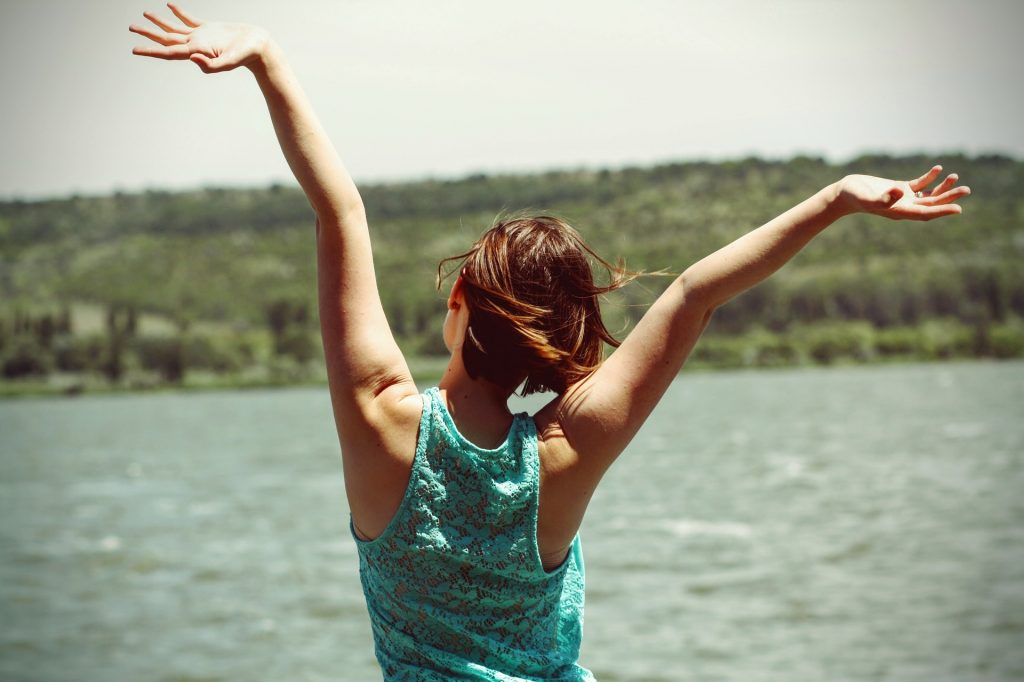 lady throwing her arms up with joy, looking over a lake, pain free